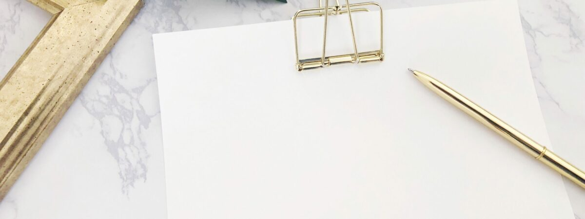 blank-paper-gold-paperclip-gold-pen-blank-gold-picture-frame-green-monstera-leaf-white-marble-table_t20_KyrNEX