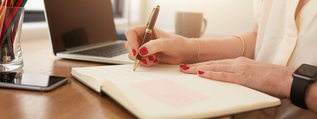 Close up image of woman sitting at her desk and writing notes. Businesswoman working at home office.
